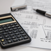 Image of calculator, paper and pen.