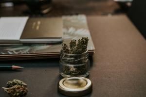 Cannabis in glass jar on desk.